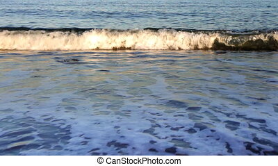waves lapping onto beach with sunlight reflections