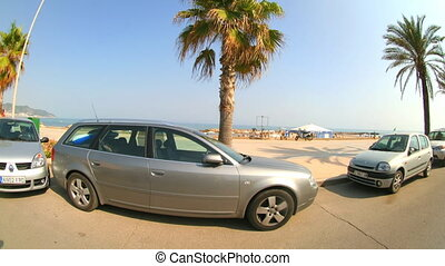 beach and parked cars shot form a moving motorbike in...