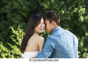 Young Adult Couple holding each other while outdoors -...