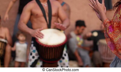 drummers play on benirras beach in ibiza as sunset starts.
