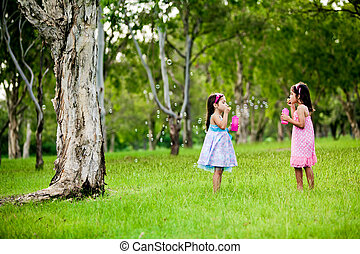 Two sisters blowing bubbles in a park