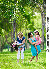 Mother, grandmother and daughters having laugh outdoors -...