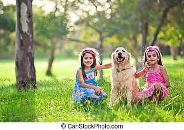 Beautiful little girls and golden retriever