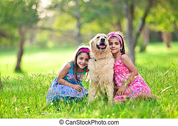 Two young girls hugging golden retriever in the park - Two...