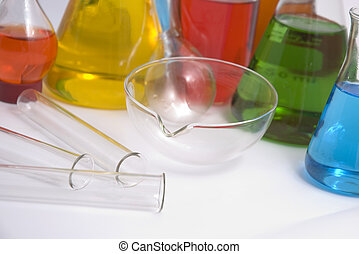 Coloured chemicals in lab bottles and glass test tubes