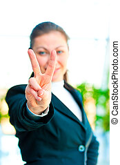 Girl in a business suit showing gesture - victory hand -...