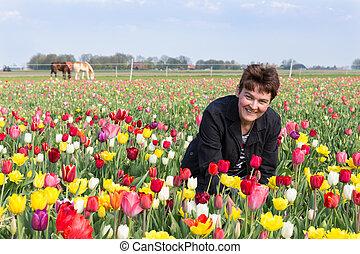 Portrait of a happy woman  in Dutch tulips field