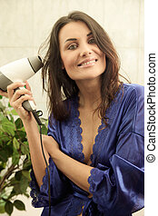 Young woman blowdrying her hair