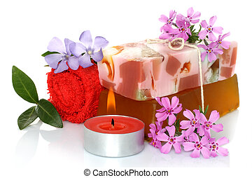 Spa composition of handmade soap, towel, flowers and candle on white background