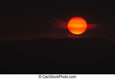 Picture of the sun as it sets over a mountain Exposed so as...