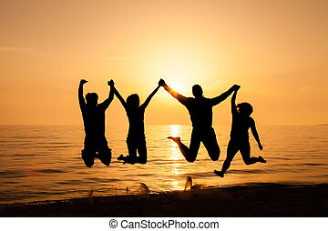 Four friends jumping on the beach at sunset