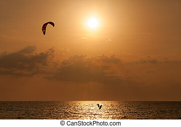 Kite surfer jumping from the water at sunset ocean