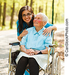 Woman in Wheelchair and a Nurse - Kind nurse taking care of...