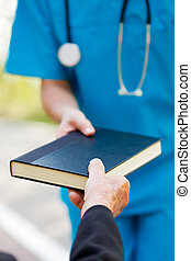 Elderly Taking Book from Nurse