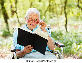Storyteller Elderly - Elderly woman in wheelchair holding...