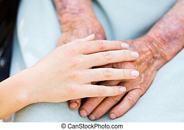 Elderly Care - Caring woman hands over elderly hands being...