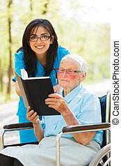 Reading Bible - Caring nurse outdoors with elderly lady...