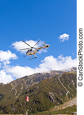 Transport helicopter fly over mountain wilderness - Small...