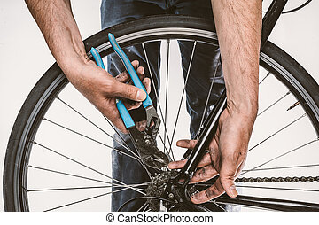 Isolated closeup of a mans grimy hands repairing a bicycle...