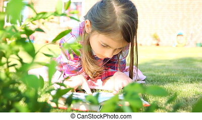 Little girl reading a book in summer on grass.Girl Reading