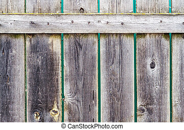 Texture of dark wood fence with vertical boards and crossbar...