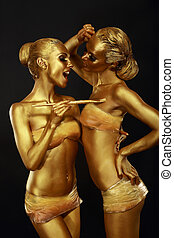 Gilt. Two Funny Women with Paintbrush. Futuristic Glossy Gold Make-up