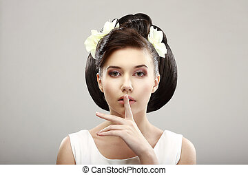 Hush! Beautiful Young Woman showing Silence Sign with her...