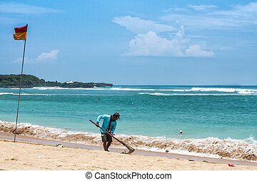 A person cleaning the beach at high resolution