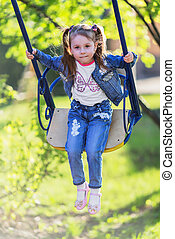 Pretty little girl swinging on seesaw in summertime