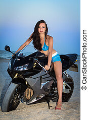 Pretty leggy brunette posing on the black motorbike