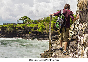 A man walking along a path at the edge of the cliff - A man...
