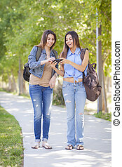 Young Adult Mixed Race Twin Sisters Sharing Cell Phone Experience Outside.