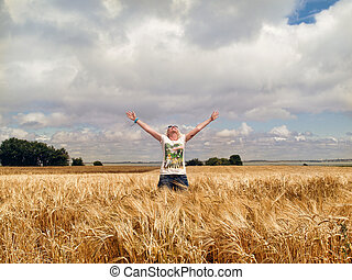 Happiness - young woman on wheat field Enjoying the sun
