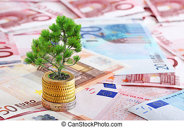 Pine tree growing from pile of coins - concept symbolizing...