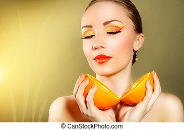 Girl with beautiful make-up holding orange fruit on yellow...