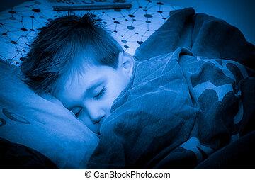 Little boy sleeping in a nice warm cozy bed