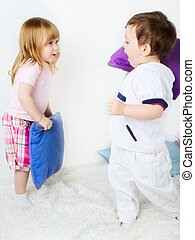 Battle of Pillows - little boy and girl playing with pillows...