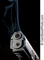 Smoking handgun - Polymer pistol on black with blue smoke...