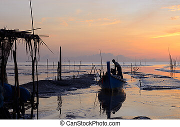 Fisherman is standing on fishing boat with sunrise background
