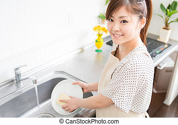 young woman washed the dishes in a kitchen