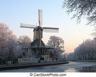 Holland, windmill at canal in winter.