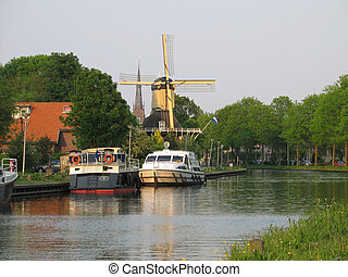 Holland, windmill at canal in month of May.