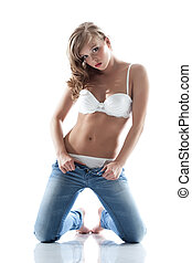 Beautiful slim girl posing taking off jeans, isolated on...