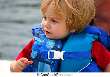 toddler in lifejacket on boat - Close-up of a young boy in a...