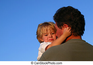 Toddler boy hugging dad - A father holds his young son will...
