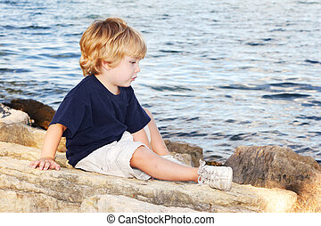 Young boy sitting by the edge of a lake