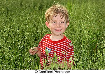 A boy standing in a field of Oats