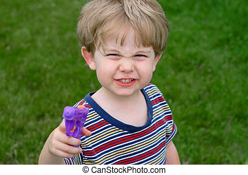Gotcha - A young boy points a water gun at the camera