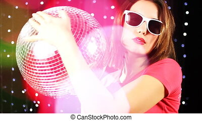 a sexy woman dances with a discoball