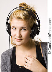music in headphones - Young woman listening to music in...